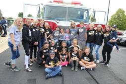 Group photo in front of fire truck with most of teammates